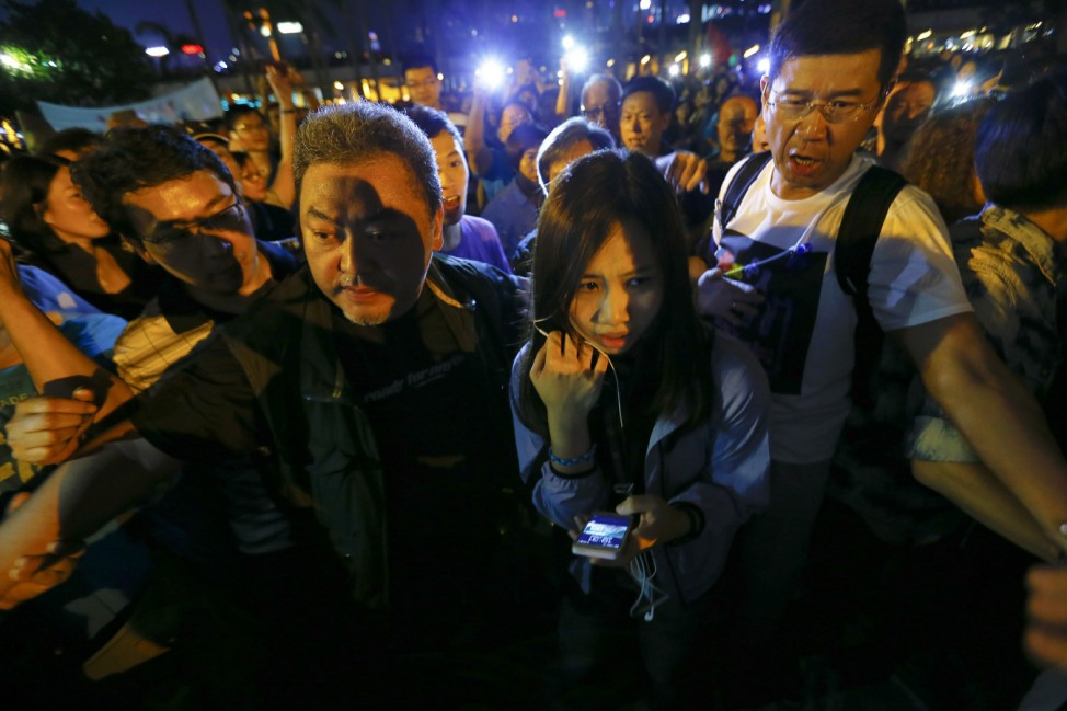 A reporter for Hong Kong's public broadcaster, RTHK, Wong Wing-yin is escorted to safety during pro-government protesters' gathering in Hong Kong