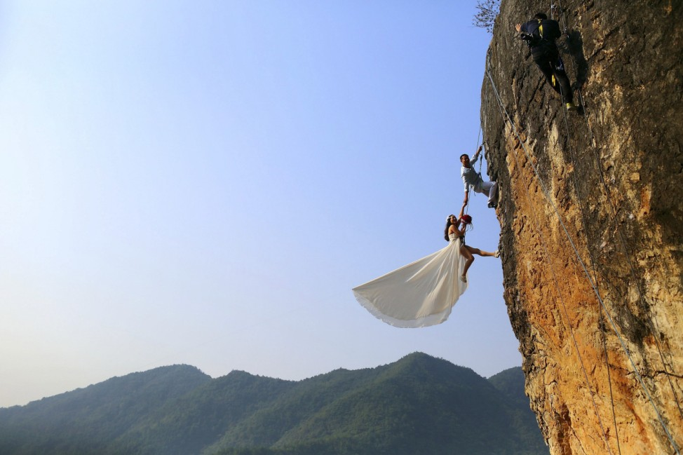 Zheng Feng, an amateur climber takes wedding pictures with his bride on a cliff in Jinhua