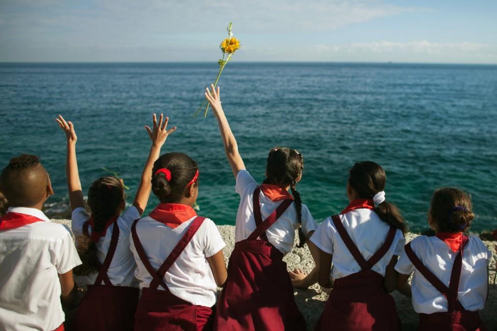 Schoolchildren throw a flower into the sea in honour of rebel revolutionary commander Camilo Cienfuegos from Havana's seafront boulevard 'Malecon'