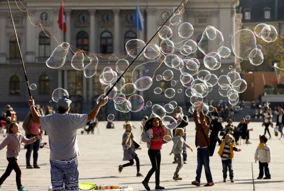 Jauch blows big soap bubbles during sunny autumn weather at a square in front of the opera house in Zurich