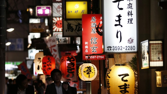 People walk past signboards of restaurants at Tokyo's business district