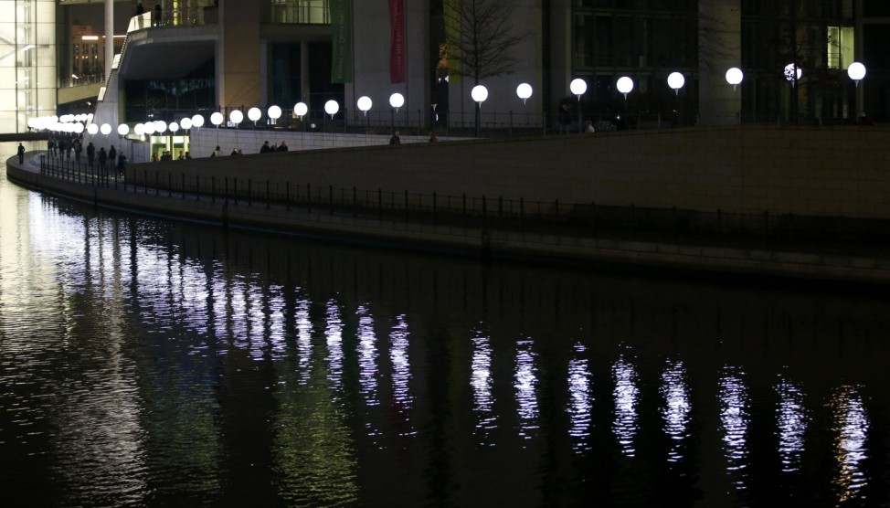 People pass by installation Border of Light along former Berlin Wall location on banks of Spree in Berlin