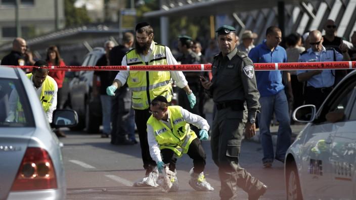 Members of the Israeli Zaka emergency response team work at the scene of a stabbing in Tel Aviv
