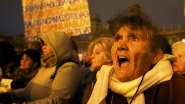 A woman shouts slogans during a protest against perceived corruption at the country's tax authority and lack of wider democratic freedoms, in front of Hungarian parliament in Budapest