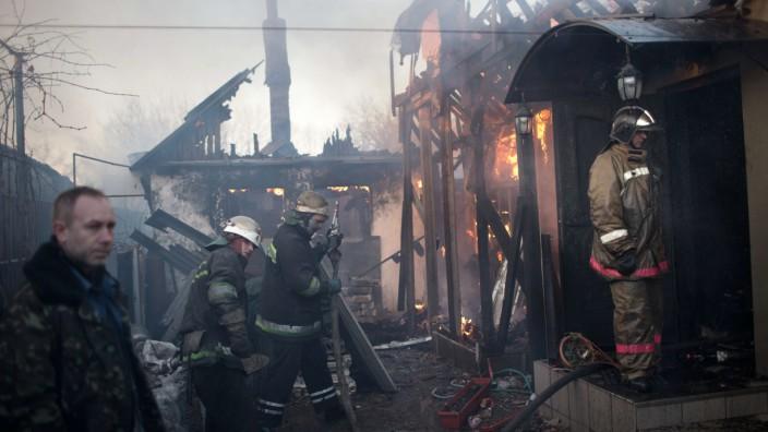 Krieg in der Ostukraine: Von wegen Waffenruhe: Feuerwehrmänner versuchen ein durch Beschuss in Brand geratenes Haus in Donezk zu löschen.
