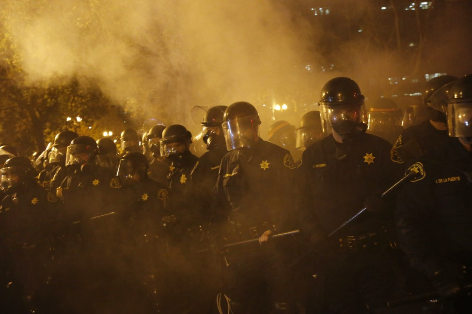 Police officers advance on demonstrators during a demonstration following the grand jury decision in the Ferguson, Missouri shooting of Michael Brown, in Oakland, California