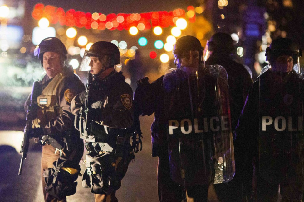 Police officers clear a street of protesters during a second night of unrest in Ferguson, Missouri