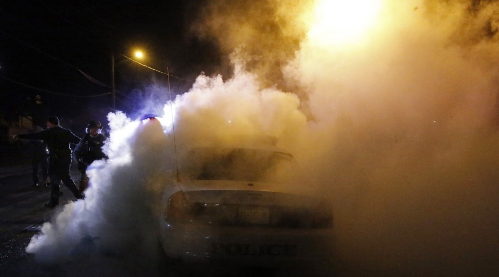 Police officers move in to extinguish a Ferguson police car set on fire by protestors in Ferguson