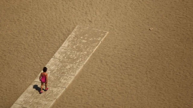Child walks toward the shore of the Malagueta beach at the Mediterranean Sea in Malaga