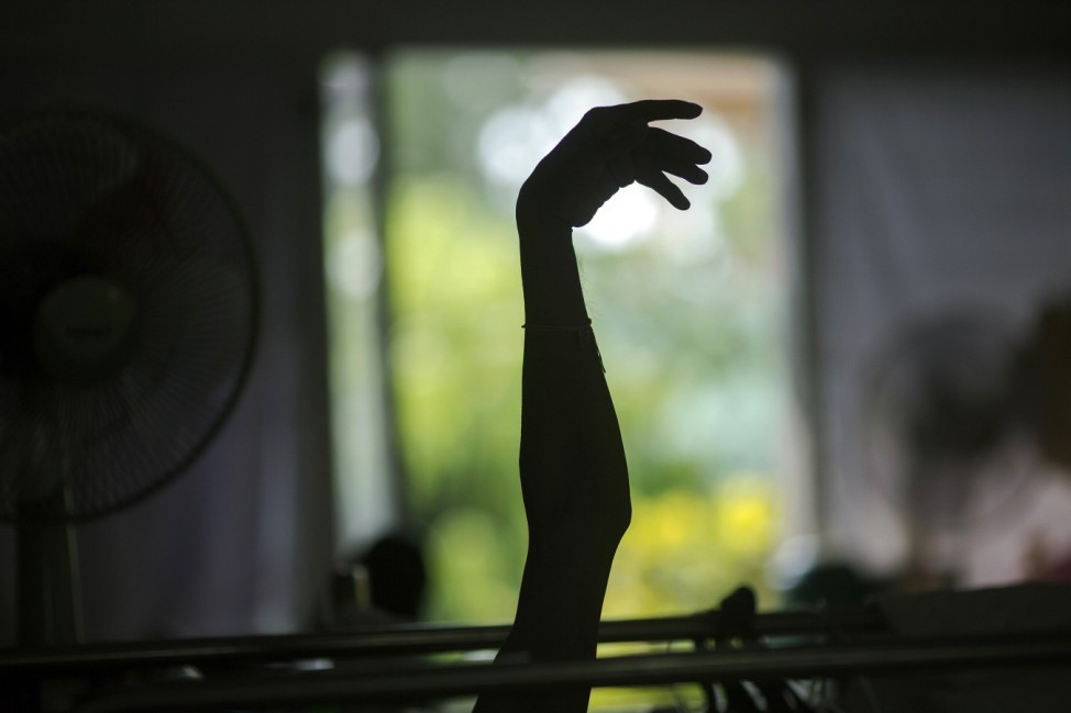 Terminally ill patient raises his arm in a hospice for those dying of AIDS at the Buddhist temple Wat Prabat Nampu in Lopburi province