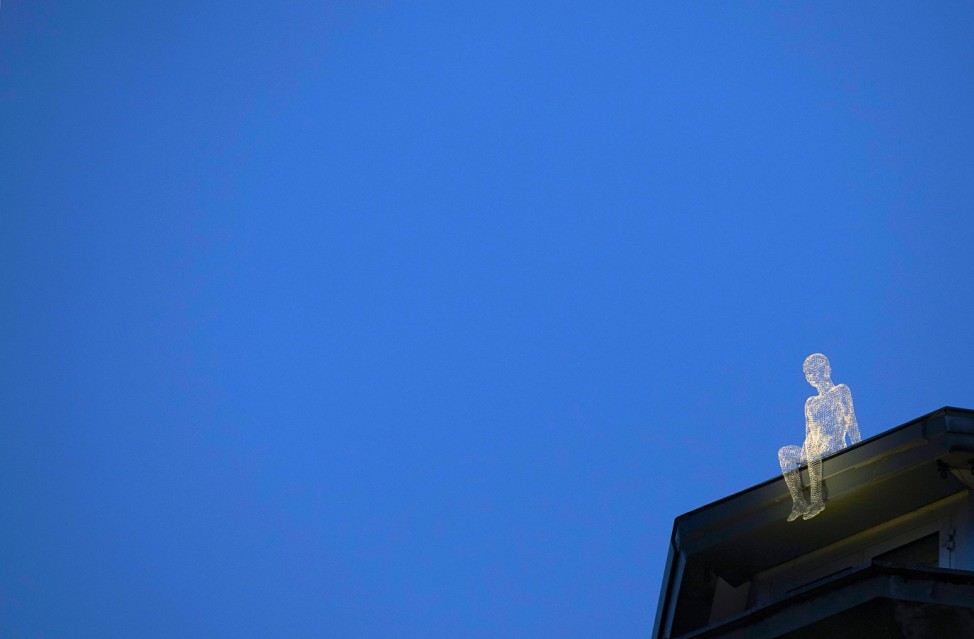 An element of the installation 'Voyageurs' by French artist Cedric Le Borgne sits atop building in Geneva
