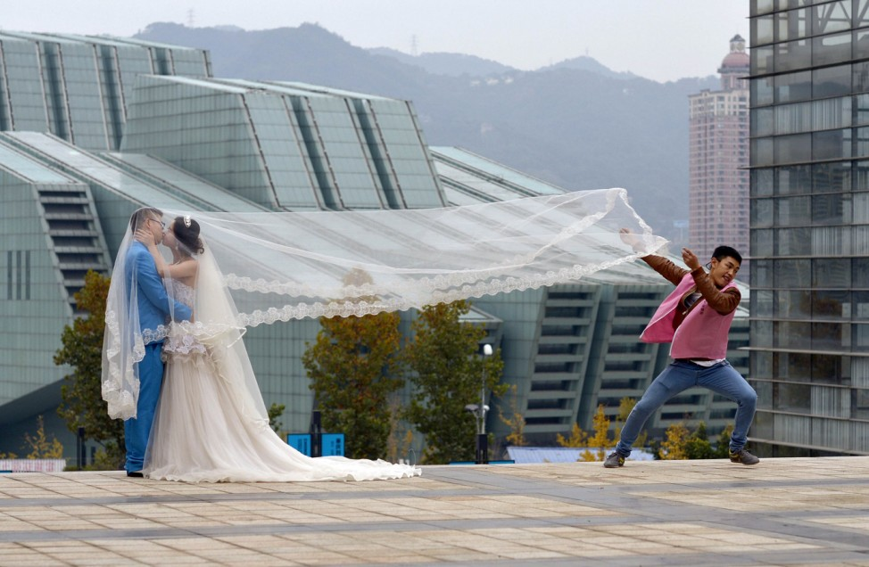 A newlywed couple kiss during a photo shoot, as an assistant runs away after lifting the veil, in Chongqing municipality