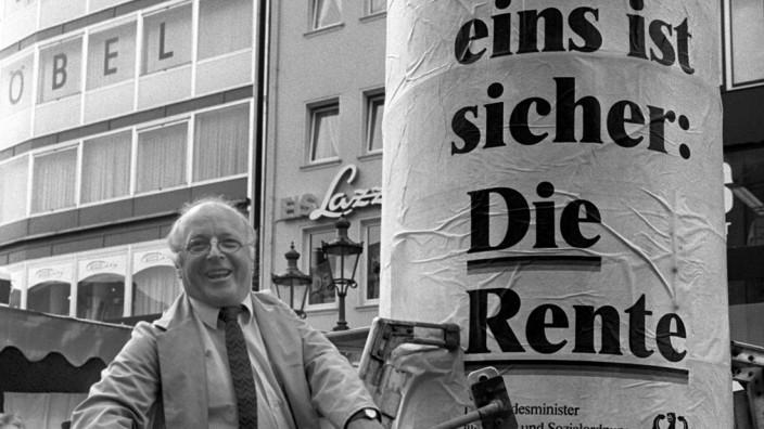 Norbert Blüm klebt Rentenplakat an Litfaßsäule