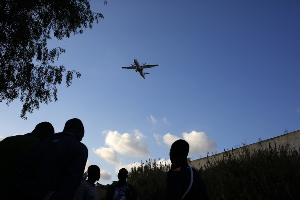 African migrants watch as an airplane flies overhead in Spain's north African enclave Melilla