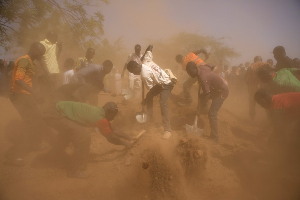 Men bury coffins of six people killed during October 30 and 31 popular uprising, during funeral service in Ouagadougou