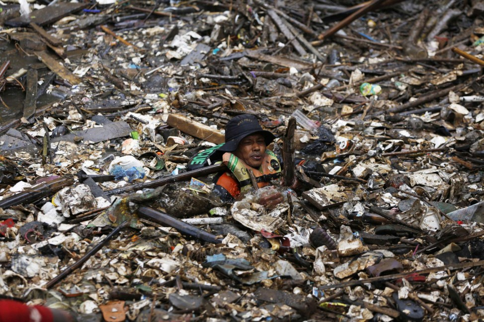 A volunteer clears rubbish from the Ciliwung River in the Jatinegara district of Jakarta