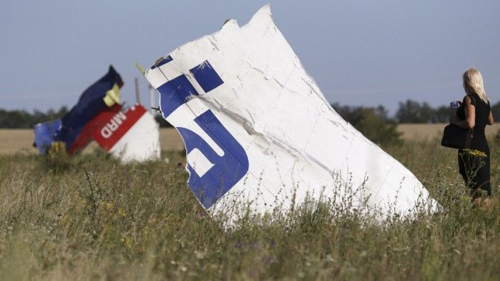 A woman takes a photograph of wreckage at the crash site of Malaysia Airlines Flight MH17 near the village of Hrabove (Grabovo)