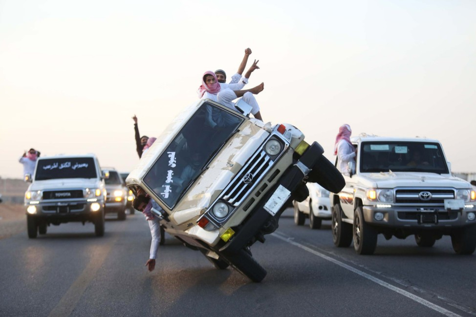 Saudi youths demonstrate a stunt known as 'sidewall skiing' (driving on two wheels) in the northern city of Tabuk