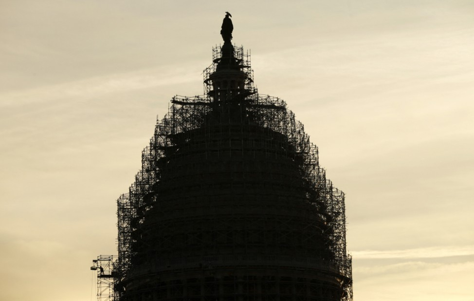 A worker reaches for supplies while working atop the scaffolded dome of the U.S. Capitol in Washington