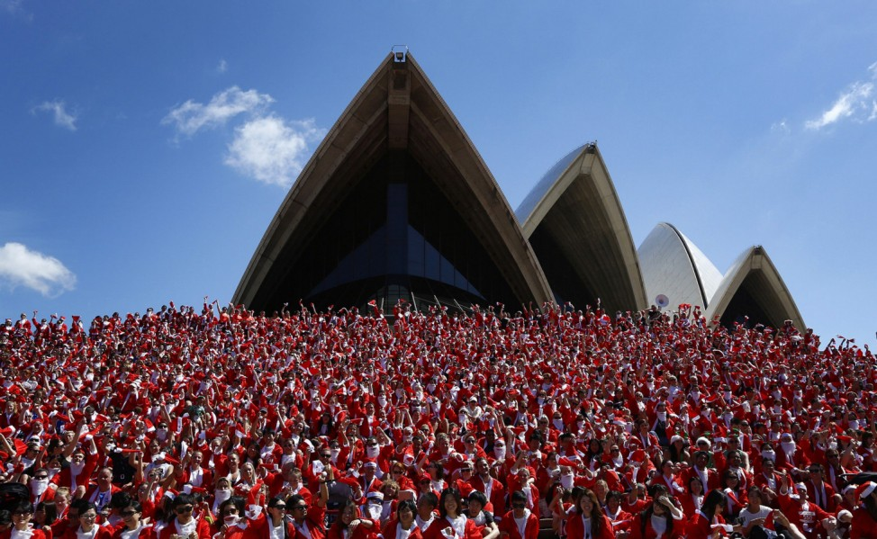 Thousands of runners in Father Christmas suits pose for a group photo after completing an annual Santa fun run from Darling Harbour to the Sydney Opera House
