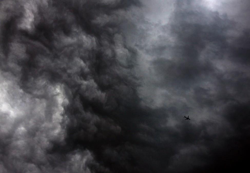 A Qantas Airways Boeing 737-800 plane flies near storm clouds above Sydney