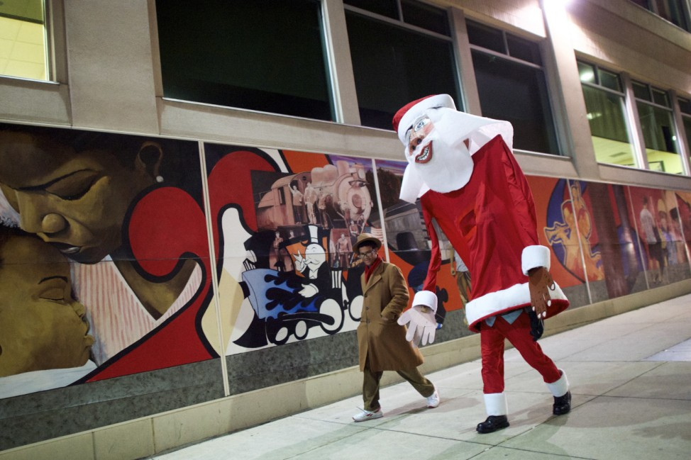 A giant Santa Claus, created and worn by local artist Ed Terrell, walks home with his son and assistant, Rupanuga, following a ceremony to decorate a scraggly Christmas tree with a single red Bulb in Reading