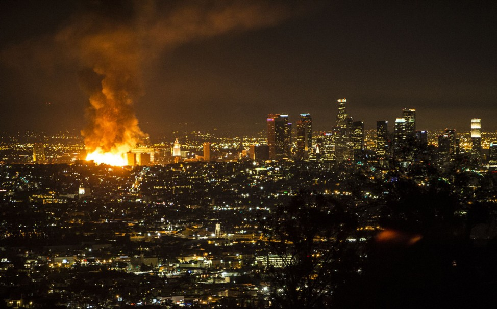 A large blaze at an apartment building under construction lights the sky near Los Angeles City Hall