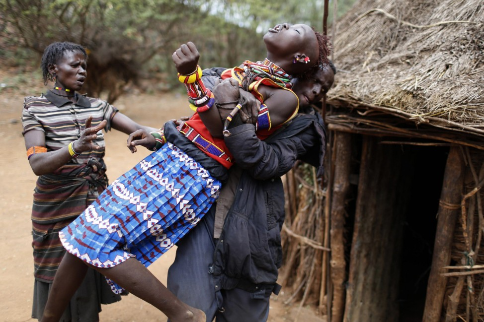 A man holds a girl as she tries to escape when she realised she is to to be married, about 80 km (50 miles) from the town of Marigat in Baringo County