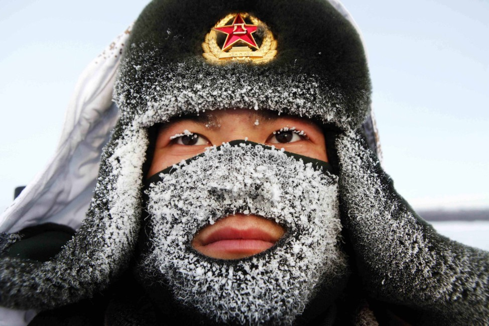 Frost covers the mask and part of the hat of a soldier of the People's Liberation Army (PLA) as he stand guard near the border of China and Russia in Heihe