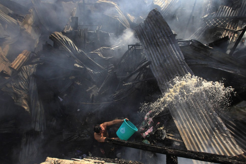A man uses a pail of water to help out firefighters as they try to put out a fire that broke out at a slum area in Manila