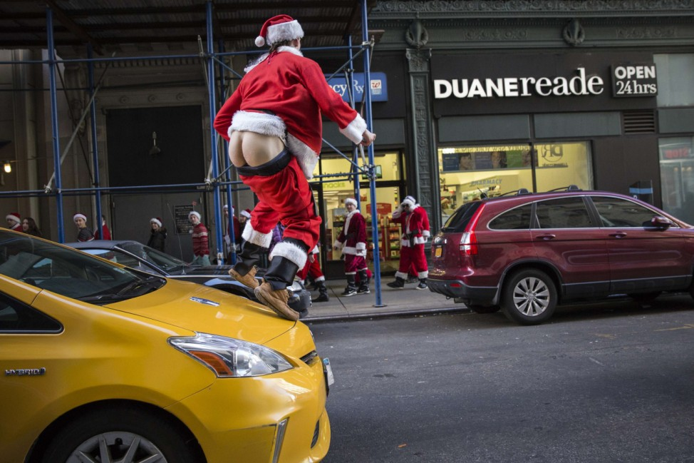 A drunken reveler jumps on a taxi with his pants down as he takes part in SantaCon through Midtown Manhattan, New York