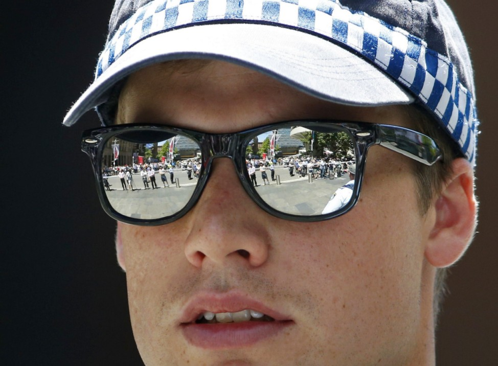 Onlookers behind a police cordon are reflected in the glasses of a police officer near Lindt cafe in Martin Place, where hostages are being held, in Sydney