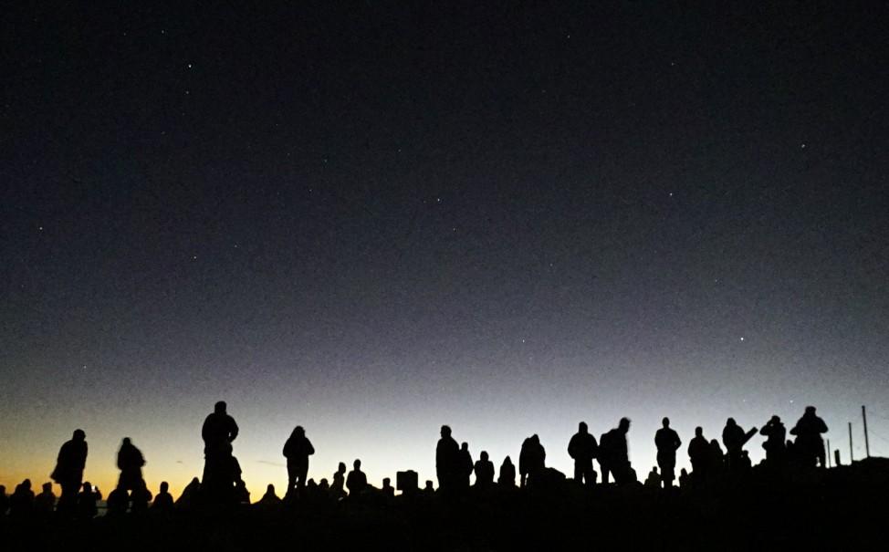 Visitors gather to watch the sunrise on the summit of the Haleakala volcano on the Hawaiian island of Maui
