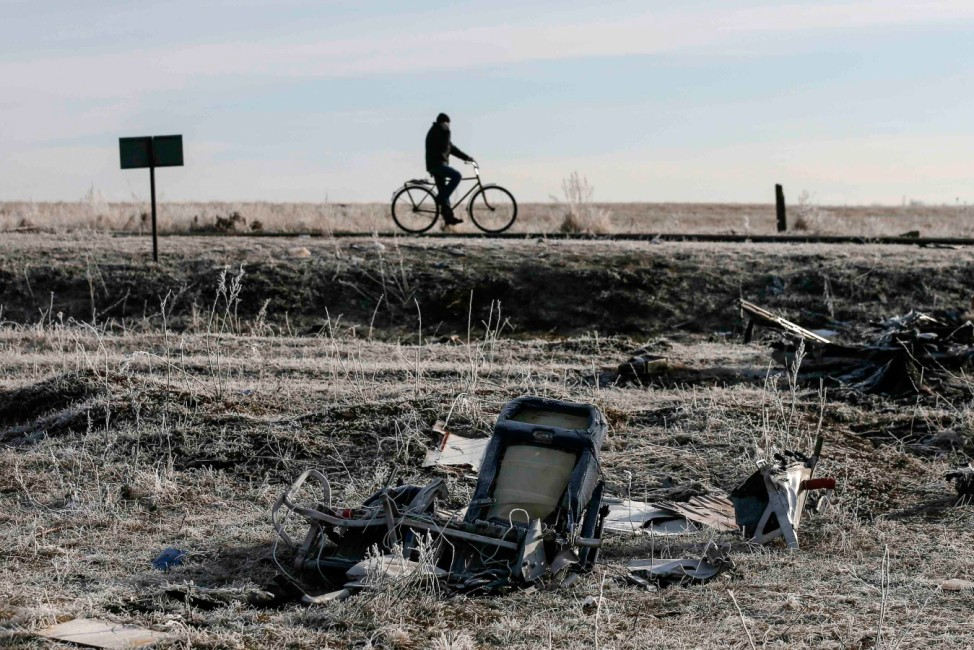 A man rides bicycle past wreckage of MH17, Malaysia Airlines Boeing 777 plane, at site of plane crash near village of Hrabove (Grabovo) in Donetsk