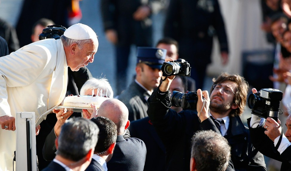 Pope Francis, who's 78th birthday is today, blows out candles on a cake as he arrives to lead his general audience at the Vatican