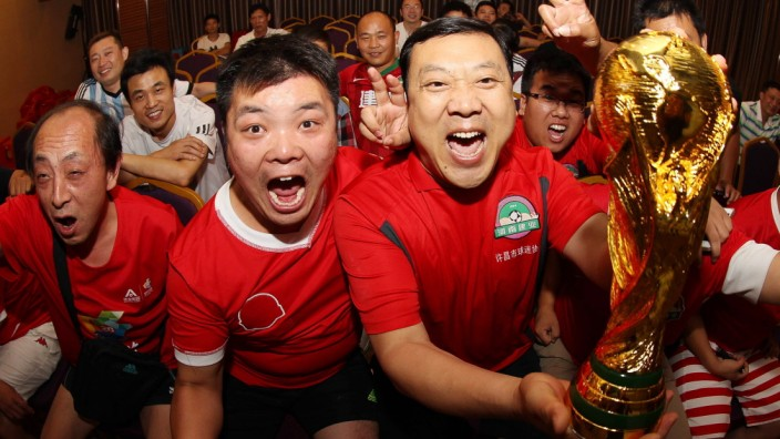 Chinese soccer fans celebrate after Germany won the World Cup as they watch the final match in Xuc