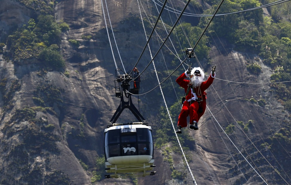 Man dressed as Santa Claus hangs on a cable for cable cars while descending from the Sugar Loaf Mountain in Rio de Janeiro