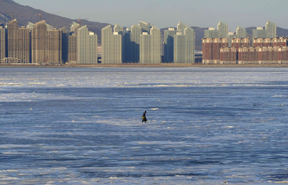 A fisherman walks on the partially frozen Jinzhou Bay of the Bohai Sea near residential construction sites, in Dalian