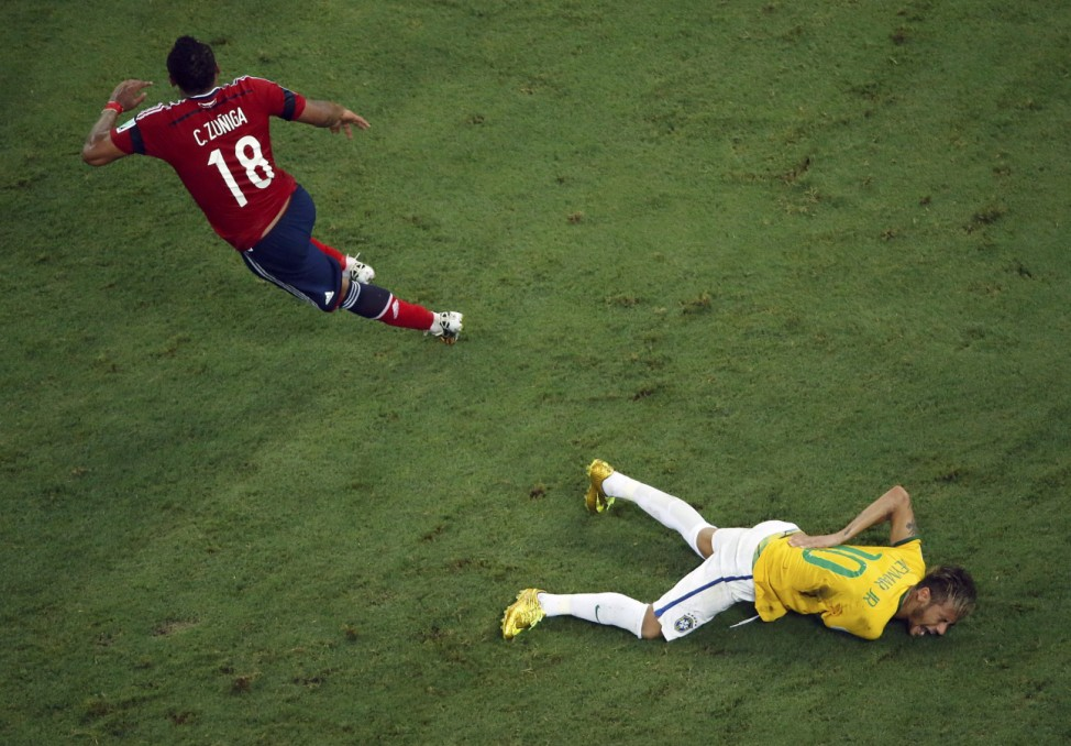 Brazil's Neymar grimaces as he lies on the ground injured after a challenge by Colombia's Zuniga during their 2014 World Cup quarter-finals at the Castelao arena in Fortaleza