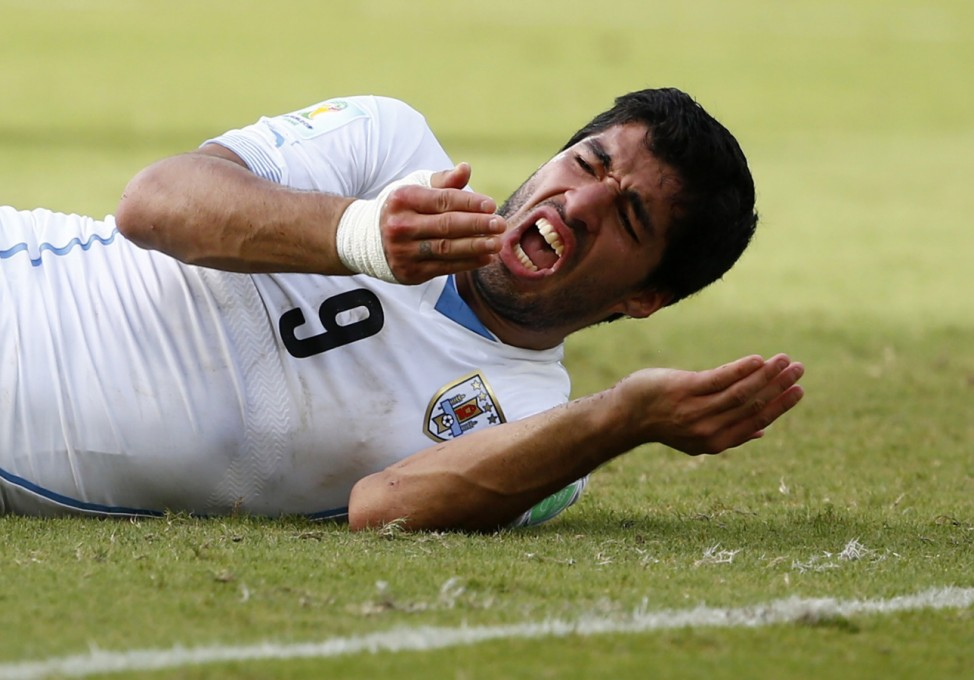 Uruguay's Luis Suarez reacts after clashing with Italy's Giorgio Chiellini during their 2014 World Cup Group D soccer match at the Dunas arena in Natal