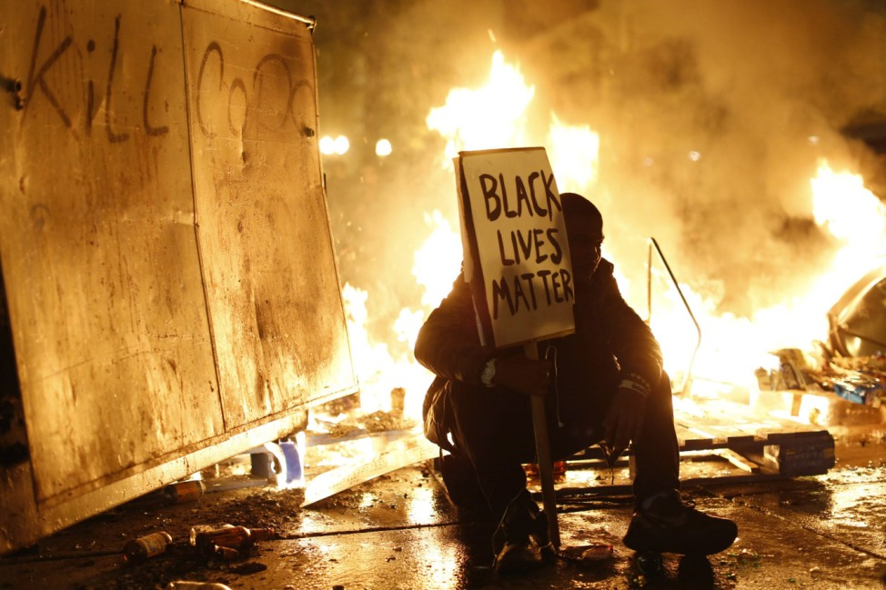 Demonstrator sits in front of a street fire during a demonstration following the grand jury decision in the Ferguson, Missouri shooting of Michael Brown, in Oakland, California