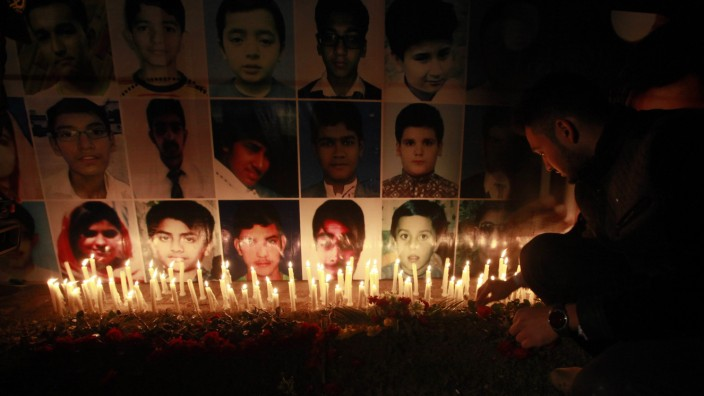 A man places a rose after lighting candles in front of portraits of the victims of the Taliban attack on the Army Public School in Peshawar, during a candlelight vigil in Lahore