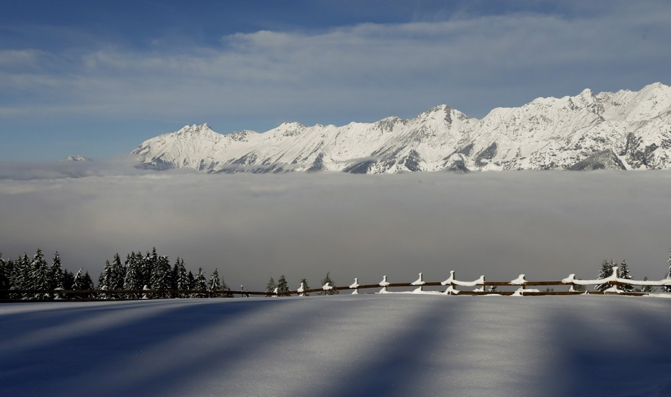 Fog covers the Inntal valley in front of snow covered mountain summits in Tulfes