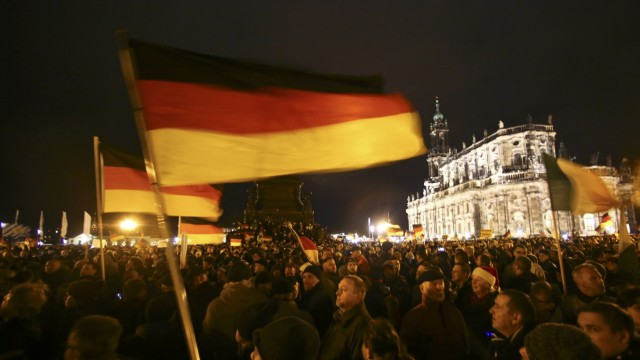 Participants hold German national flags during a demonstration called by anti-immigration group PEGIDA, a German abbreviation for 'Patriotic Europeans against the Islamization of the West', outside Semperoper opera house in Dresden
