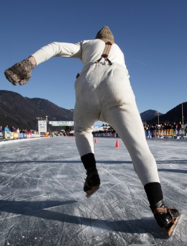 A participant in the Frisian Shorttrack Championships wears traditional clothing and wooden skates as he starts skating during the race in Techendorf