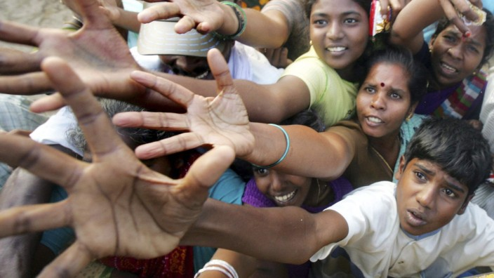 File photo of tsunami survivors rushing for clothes and food donated by volunteer organisations in Cuddalore