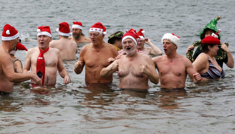 Members of Berlin's ice swimming club sing as they a dip in the Orankesee lake as part of their traditional Christmas ice swimming session