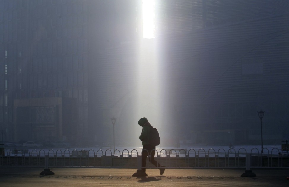 A pedestrian walks past a beam of sunlight cast through two buildings amid heavy smog in Shenyang