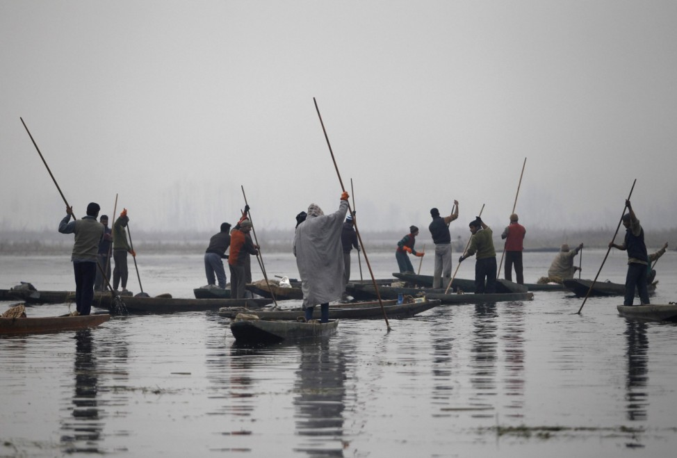 Kashmiri fishermen use spears to catch fishes in the waters of the Anchar Lake on a cold winter day in Srinagar