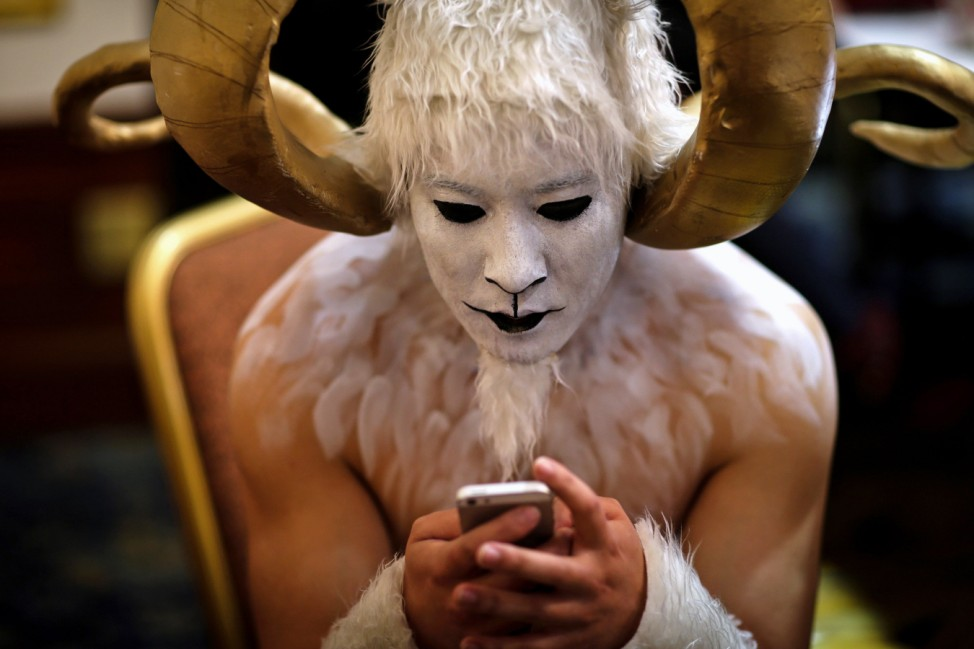 A performer in a ram costume looks at his phone backstage during a performance in Kunming